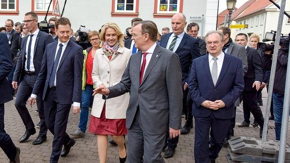 Mehrere Politiker gehen gemeinsam eine Straße entlang.