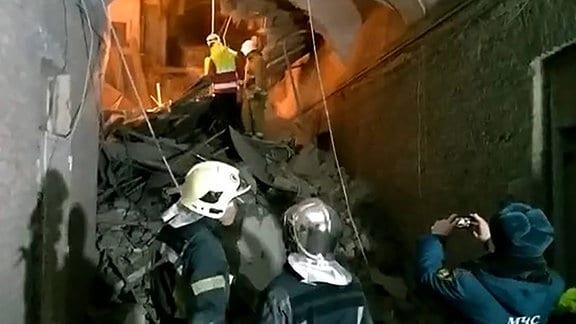 Einsatzkräfte der Feuerwehr vor Trümmern in Gebäuder der Universität St. Petersburg