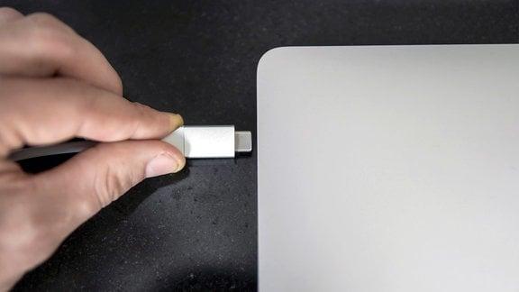 Männliche Hand, die ein weißes USB-C-Typ-C-Kabel in einen Anschluss an einem grauen Laptop einsteckt.
