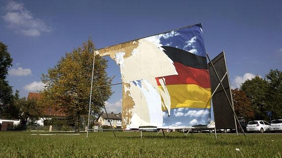 Ein Wahlplakat zur Bundestagswahl 2017 ist fast komplett zerstört und heruntergerissen.