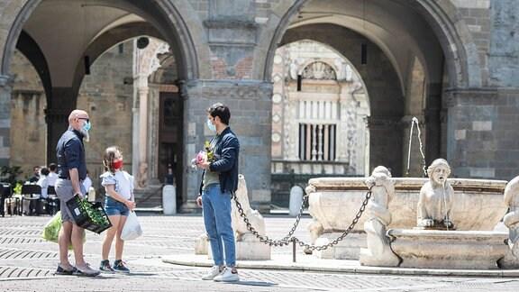 Menschen mit Mundschutz im Zentrum von Bergamo