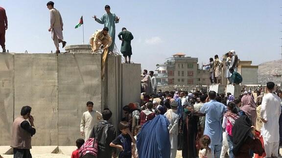 Menschen versuchen die Mauer des Flughafens ins Kabul zu überwinden.