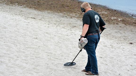 Mann sucht einen Strand mit einem Metalldetektor ab.