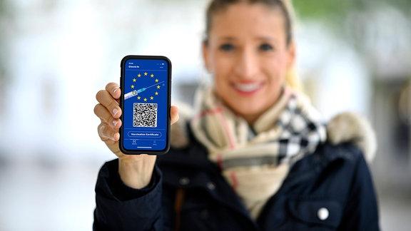 Frau zeigt Smartphone mit digitalem europäischen Impfpass mit QR-Code