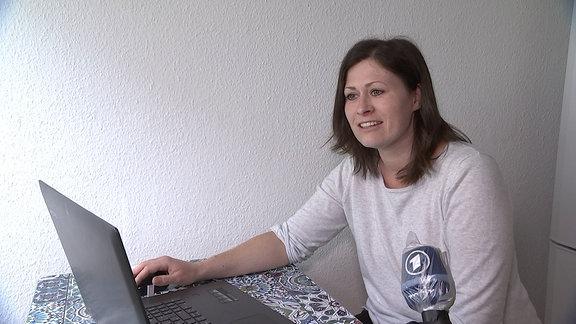 Eine junge Frau sitzt an einem kleinen Tisch mit einem Laptop darauf