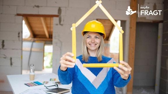Eine junge Frau mit gelbem Helm und zum Haus geformten Zollstock auf einer Baustelle
