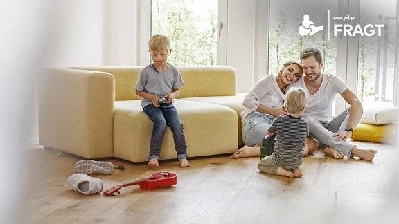 Zwei Jungen mit den Eltern in einem Wohnzimmer