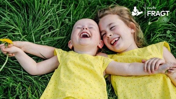 Zwei Mädchen liegen im Gras