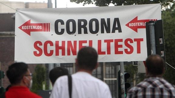 MEnschen stehen vor einem Corona Testzentrum an.