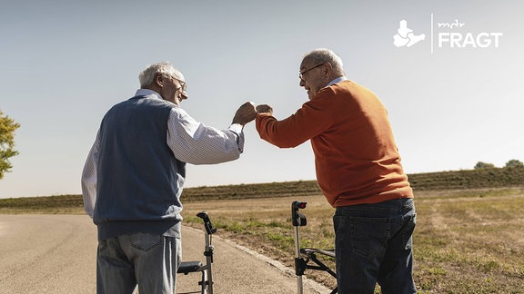 """Zwei ältere Männer mit Rollator begrüßen sich mit einem """"Faust-Schlag"""" statt die Hand zu geben."""
