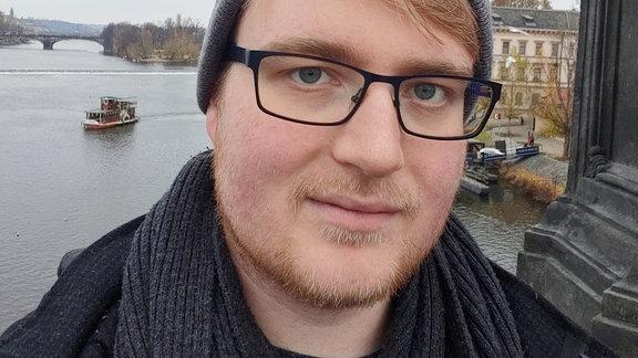 Mann mit Brille steht im Freien
