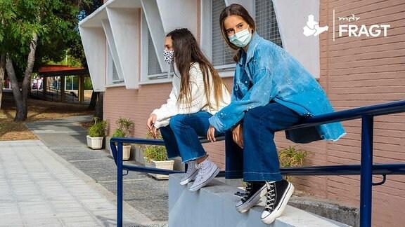 Zwei Mädchen sitzen mit Maske auf einem Treppengeländer