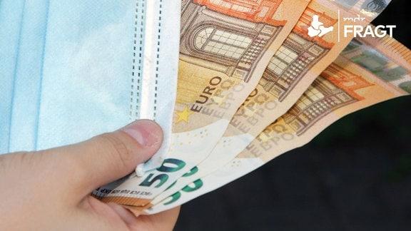 Eine Hand hält Geldscheine und eine Gesichtsmaske