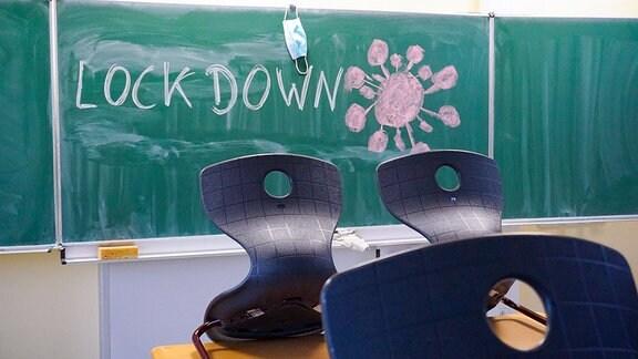 An eine Schultafel in einem Klassenzimmer wurde mit Kreide das Wort Lockdown geschrieben und ein Virussymbol gemalt. An der Tafel hängt eine Mund-Nasenmaske. Im Vordergrund sind die Stühle auf die Tische gestellt.