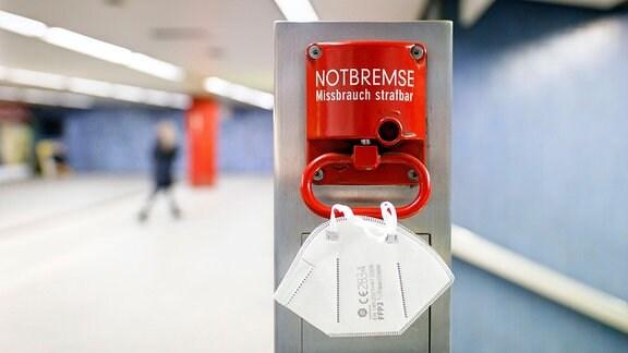 An einer Notbremse in einer Bahnhaltestelle hängt eine FFP2-Maske