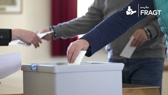 Ein Wähler steckt im Wahlbuero ein Wahlumschlag in eine Wahlurne.