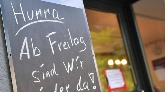 Auf Restauranttafel steht mit Kreide geschrieben: 'Hurra - Ab Freitag sind wir wieder da!'