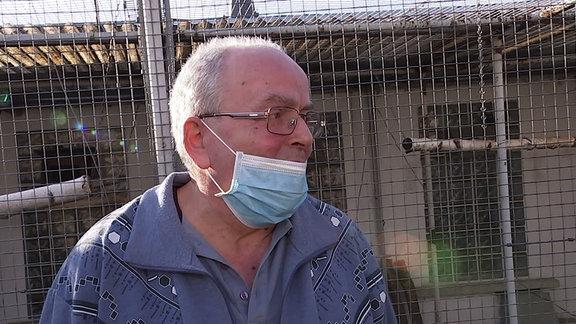 Ein Mann mit Mundschutz vor einem Vogelkäfig