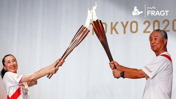 Mann und Frau mit dem Olympischen Feuer