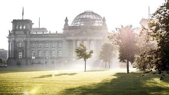 Der Reichstag zeichnet sich ab vor der aufgehenden Sonne in Berlin.