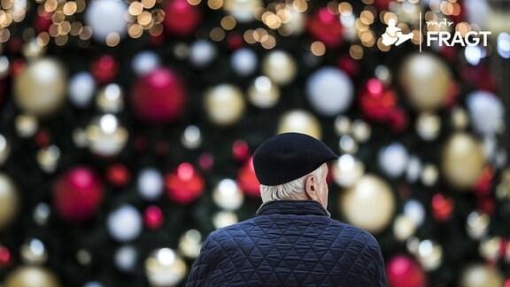 Ein Mann sitzt allein auf einer Bank vor einem geschmückten Weihnachtsbaum