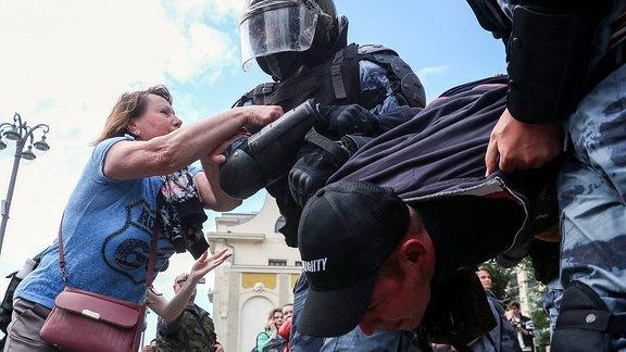 Russische Polizisten verhaften Demonstranten.