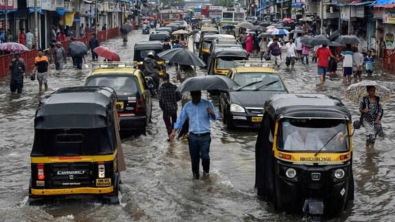 Die Menschen gehen entlang einer überfluteten Straße nach starken Regenschauern außerhalb der Kurla-Station in Mumbai, Indien.