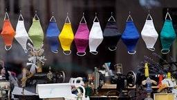 Verschiedene Masken aus Stoff hängen im Fenster einer Schneiderei | imago images/Future Image