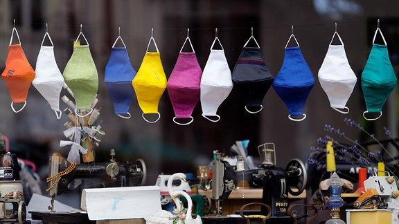 Verschiedene Masken aus Stoff hängen im Fenster einer Schneiderei