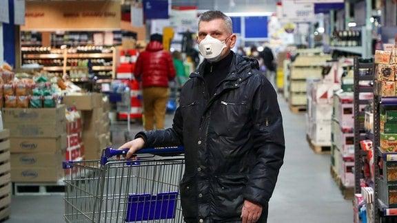 Ein Mann mit einem Mundschutz in einem Supermarkt