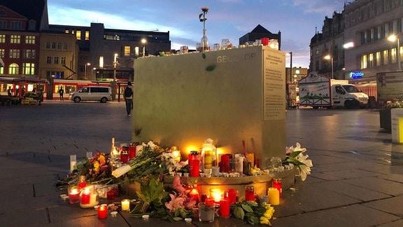 Blumen und Kerzen liegen nach dem Angriff auf die Synagoge in Halle mit zwei Toten am Vortag am Geoskop auf dem Marktplatz.