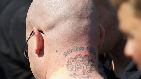 Ein Neoanzi-Skinhead mit einem Tattoo der rechtsradikalen Nazi-Organisation Weisse Wölfe und einem Schlagring mit dem Kuerzel C18,  2012