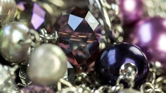 Modeschmuck mit farbigen Perlen als Nahaufnahme auf dunklem Hintergrund.