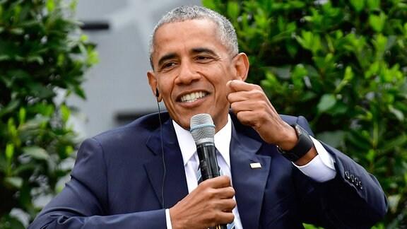 Ein Mann sitzt in einem Sessel und spricht in ein Mikrofon.