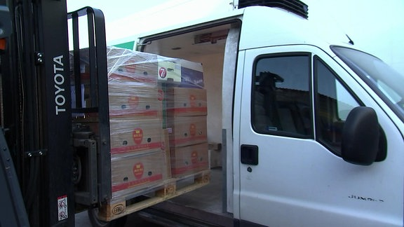 Ein Gabelstapler lädt Lebensmittel in einen Transporter