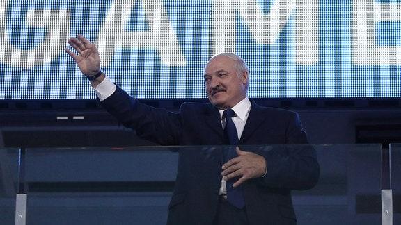 """Alexander Lukaschenko hebt grüßend den Arm. Auf einer Stadionanzeige hinter ihm steht """"Game""""."""
