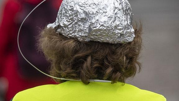 Einen bei Verschwörungstheoretikern beliebten und oft ironisierten «Aluhut» trägt die Teilnehmerin an einer Kundgebung