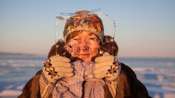Eine Frau sieht durch eine Eisplatte