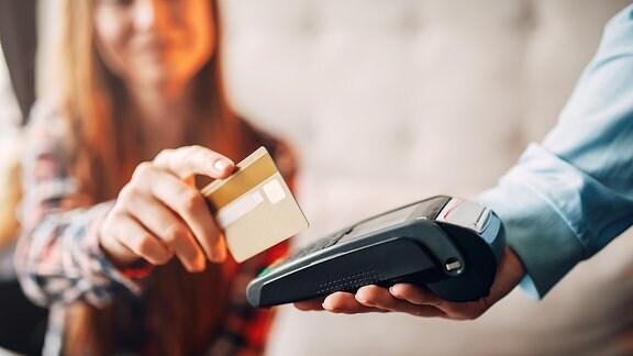 Eine Frau zahlt bargedllos mit einer Kreditkarte