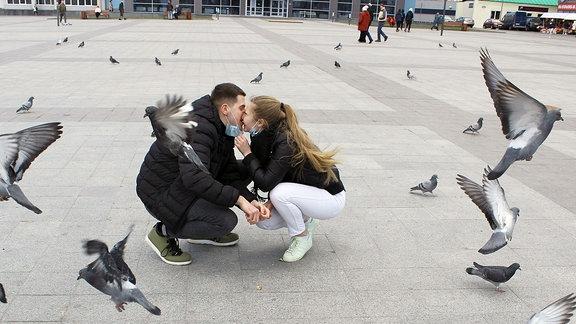 ein Paar mit Masken und Tauben