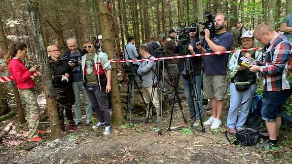 Kamerateams stehen im Wald hinter einer Absperrung