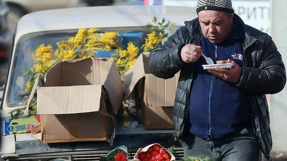 Blumenhändler während Mittagspause isst etwas an seinem Stand aus einer Schale.