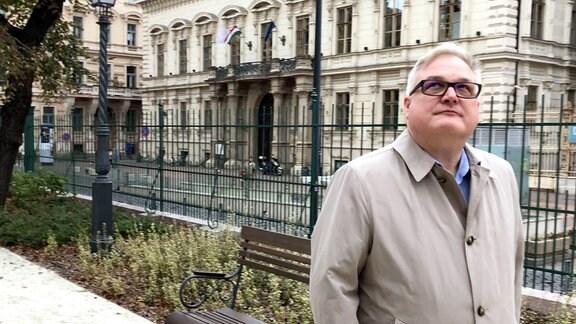 Mann mit grauen Haaren, Mantel und Brille läuft vor einem Palais entlang.