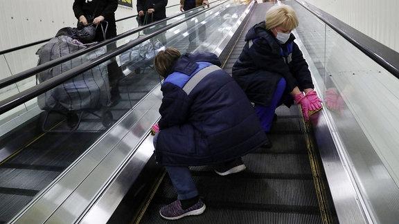Desinfektion einer Rolltreppe als Teil der vorbeugenden Maßnahmen gegen die Ausbreitung des neuartigen Coronavirus.