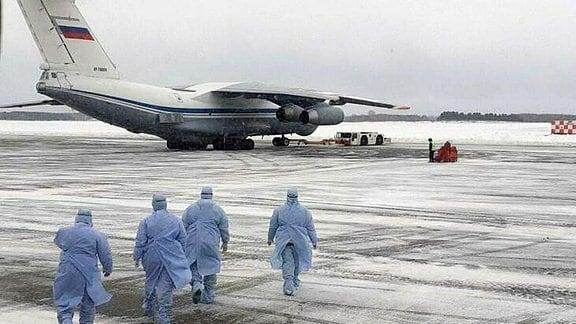 Männer mit Schutzkleidung gehen zu einer Ilyushin IL-76.