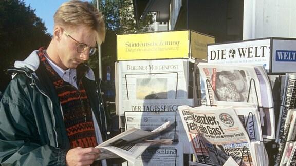 Ein Mann liest an einem Kiosk eine Zeitung