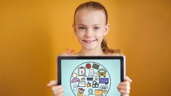 Ein Mädchen hält ein Tablet in den Händen.