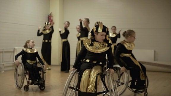 drei Kinder in Rollstühlen und schwarz-goldenen Gewändern bei einer Tanzstunde.