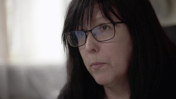 Dunkelhaarige Frau mit Brille in Nahaufnahme.