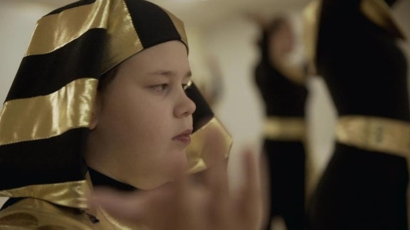 Junge in schwarz-goldenem Gewand in Nahaufname.